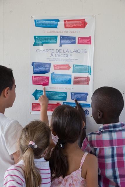 enfants montrant la charte de la laïcité accrochée sur le mur d'une école